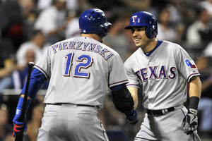 Photo - Texas Rangers' Ian Kinsler right, celebrates with teammate A.J. Pierzynski (12), at home plate after hitting an inside-the-park home run during the third inning of a baseball game against the Chicago White Sox in Chicago, Friday, Aug. 23, 2013. (AP Photo/ Paul Beaty)