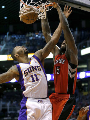 Photo - Toronto Raptors' Amir Johnson (15) dunks over Phoenix Suns' Markieff Morris (11) during the first half of an NBA basketball game, Wednesday, March 6, 2013, in Phoenix.  (AP Photo/Matt York)