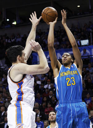 Photo - New Orleans Hornets' Anthony Davis (23) shoots over Oklahoma City Thunder forward Nick Collison (4) in the first quarter of an NBA basketball game in Oklahoma City, Wednesday, Dec. 12, 2012. (AP Photo/Sue Ogrocki)