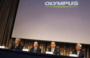 Photo -   FILE - In this Feb. 27, 2012 file photo, newly-appointed President of Olympus Corp. Hiroyuki Sasa, left, speaks as his predecessor Shuichi Takayama, second left, and two outside directors of the company, Hiroshi Kuruma, second right, and Yasuo Hayashida, attend a press conference in Tokyo when the entire board of scandal-tainted Olympus resigned and the new president was tapped to lead a turnaround at the Japanese medical equipment maker. Sony and Olympus have agreed on a business alliance that will see Sony Corp. invest 50 billion yen ($640 million) for an 11 percent stake in the embattled medical equipment and camera company. Olympus has been on shaky ground after its British chief executive turned whistleblower and helped unearth a scandal involving a systematic cover-up of massive losses. (AP Photo/Koji Sasahara)