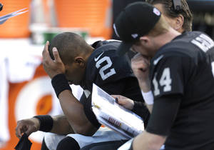 Photo - Oakland Raiders quarterback Terrelle Pryor (2) sits on the bench next to quarterback Matt McGloin (14) during the second half of an NFL football game against the Denver Broncos in Oakland, Calif., Sunday, Dec. 29, 2013. (AP Photo/Tony Avelar)