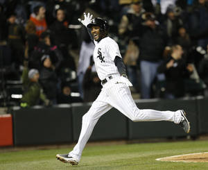 Photo - Chicago White Sox's Alexei Ramirez celebrates after scoring the game-winning run off a throwing error by Boston Red Sox shortstop Xander Bogaerts during the ninth inning of a baseball game Tuesday, April 15, 2014, in Chicago. Chicago won 2-1. (AP Photo/Charles Rex Arbogast)