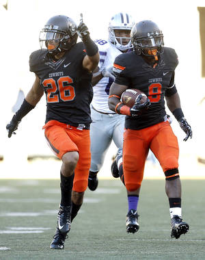 Photo - OSU's Tyler Patmon, left, provides blocking for Daytawion Lowe, as Lowe returns an interception late in the fourth quarter to secure a 33-29 win over Kansas State on Saturday at Boone Pickens Stadium. Photo by Sarah Phipps, The Oklahoman