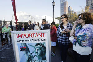Photo - Tourists who had hoped to visit the Statue of Liberty stand near the dock used by Liberty Island ferries, Tuesday, Oct. 1, 2013 in New York. A government shutdown, the first since the winter of 1995-96, closed national parks across the nation. (AP Photo/Mark Lennihan)