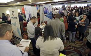 Photo - FILE - In this Wednesday, Aug. 14, 2013 file photo, job seekers check out companies at a job fair in Miami Lakes, Fla. The Labor Department reports on the number of Americans who applied for unemployment benefits on Thursday, Oct. 3, 2013.  (AP Photo/Alan Diaz, File)