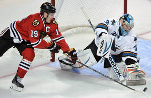 Photo - San Jose Sharks goalie Alex Stalock, right, makes a save against Chicago Blackhawks' Jonathan Toews (19) during the third period of an NHL hockey game in Chicago, Sunday, Jan. 5, 2014. San Jose won 3-2 in a shootout. (AP Photo/Paul Beaty)