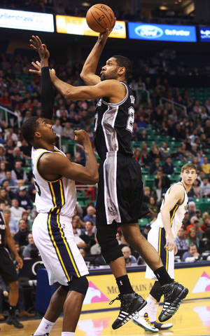 Photo - San Antonio Spurs' Tim Duncan, right, shoots the ball as Utah Jazz's Derrick Favors, left, defends in the first half of an NBA basketball game on Saturday, Dec. 14, 2013, in Salt Lake City. (AP Photo/Kim Raff)