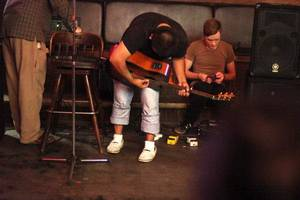 Photo - A 25-year-old college student tunes his guitar at the Crystal Pistol before playing a show in downtown Tulsa. He came to the U.S. illegally with his mother at age 14 from Mexico to join his father. <strong>Adam Wisneski - Tulsa World</strong>