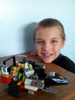Photo -  At right: Porter Trammell, 10, shows a Lego creation he built. Porter survived the May 20, 2013, tornado at Plaza Towers Elementary School, but was denied admission to the school this year because his home hasn't been rebuilt. Photo provided  <strong></strong>