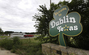 Photo - In this June 14, 2014 photo, a shamrock sign welcomes drivers to Dublin, Texas.  Most of Dublin's 3,887 residents believe the connection to Ireland is mythical, and that their town is more likely named after the settler expression for seeking protection from Plains attackers by circling their wagons at night, or doublin' up. (AP Photo/LM Otero)