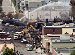 Photo -  Searchers dig through the rubble for victims of an inferno July 8 in Lac-Megantic, Quebec,  as firefighter continue to hose down tanker cars to prevent explosions. A runaway train derailed igniting tanker cars carrying crude oil early July 6.  AP File Photo  <strong>Ryan Remiorz - AP</strong>
