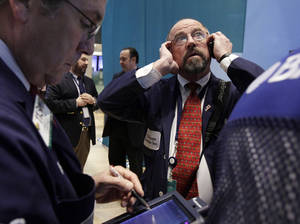 photo - FILE - In this Tuesday, Dec. 11, 2012, file photo, Trader Frederick Reimer, right, works on the floor of the New York Stock Exchange. Stocks opened close to break-even Thursday after the government said weekly applications for unemployment benefits fell to the second-lowest level this year. (AP Photo/Richard Drew, file)