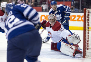 Photo - Toronto Maple Leafs left winger Mason Raymond, left, scores on Montreal Canadiens goaltender Carey Price as Joffrey Lupul (19) watches during the second period of an NHL hockey game Saturday, Jan. 18, 2014, in Toronto. (AP Photo/The Canadian Press, Frank Gunn)