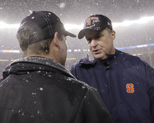 Photo - Syracuse coach Doug Marone, right, greets West Virginia coach Dana Holgorsen after Syracuse defeated West Virginia 38-14 in the Pinstripe Bowl NCAA college football game at Yankee Stadium in New York, Saturday, Dec. 29, 2012. (AP Photo/Kathy Willens)