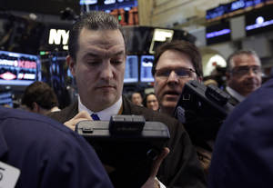 Photo - FILE - In this  Friday, March 7, 2014, file photo, trader Theodore Nelson, left, works on the floor of the New York Stock Exchange. World stock markets sank Wednesday March 12, 2014 as recent falls in Chinese copper and iron prices added to jitters that the world's No. 2 economy is continuing to slow. (AP Photo/Richard Drew, File)