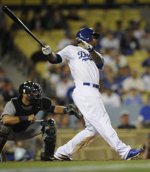 Photo - Los Angeles Dodgers' Carl Crawford, center follows through on his hit for a walk off double to score Los Angeles Dodgers' Chone Figgins during the 10th inning of a baseball game against the Detroit Tigers in Los Angeles, Tuesday, April 8, 2014. The Los Angeles Dodgers won 3-2. (AP Photo/Kelvin Kuo)