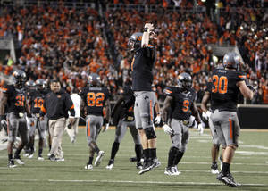Photo - Oklahoma State's Brandon Weeden (3) celebrates Joseph Randle's winning touchdown during a college football game between the Oklahoma State University Cowboys (OSU) and the Kansas State University Wildcats (KSU) at Boone Pickens Stadium in Stillwater, Okla., Saturday, Nov. 5, 2011.  Photo by Sarah Phipps, The Oklahoman
