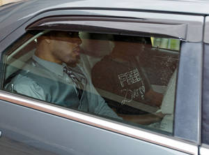 photo - Former Oklahoma State basketball player Darrell Williams, foreground, is driven away from the Payne County Jail in Stillwater, Okla., Friday, Oct. 12, 2012, after he avoided more time behind bars when a judge gave him a suspended sentence in a sexual assault case in which Williams insisted he was innocent. His brother, Pierre, is at right. (AP Photo/Sue Ogrocki)