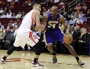 Photo - Los Angeles Lakers' Kobe Bryant (24) pushes against Houston Rockets' Jeremy Lin, left, in the first half of an NBA basketball game, Tuesday, Dec. 4, 2012, in Houston. (AP Photo/Pat Sullivan)