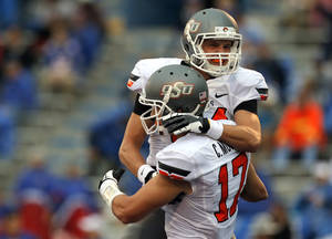 Photo - Oklahoma State's Austin Hays celebrates a touchdown with Oklahoma State's Charlie Moore (17) during the college football game between Oklahoma State University (OSU) and the University of Kansas (KU) at Memorial Stadium in Lawrence, Kan., Saturday, Oct. 13, 2012. Photo by Sarah Phipps, The Oklahoman