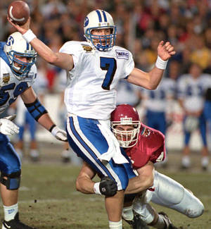 Photo - BYU quarterback John Walsh gets a pass away before being brought down by Oklahoma's Brent DeQuasie during the 1994 Copper Bowl. AP photo