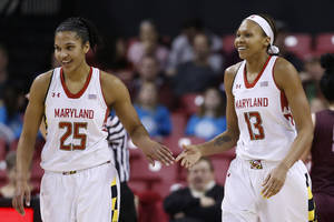 Photo - Maryland forward Alyssa Thomas, left, and center Alicia DeVaughn high-five during a break in play in the first half of an NCAA college basketball game against Virginia Tech in College Park, Md., Sunday, March 2, 2014. (AP Photo/Patrick Semansky)