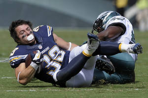 Photo - San Diego Chargers' Danny Woodhead, left, loses his helmet as he is tackled by Philadelphia Eagles' DeMeco Ryans during the first half of an NFL football game on Sunday, Sept. 15, 2013, in Philadelphia. (AP Photo/Michael Perez)