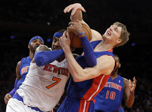 Photo - Detroit Pistons' Kyle Singler (25) fights for control of the ball with New York Knicks' Carmelo Anthony (7) during the first half of an NBA basketball game Tuesday, Jan. 7, 2014, in New York.  (AP Photo/Frank Franklin II)