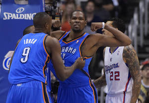 Photo - Oklahoma City Thunder forward Kevin Durant, center, flexes after being fouled in the first half of Game 4 of the Western Conference semifinal NBA basketball playoff series against the Los Angeles Clippers, Sunday, May 11, 2014, in Los Angeles. Thunder forward Serge Ibaka, of Congo, grabs Durant as Clippers forward Matt Barnes looks on. (AP Photo/Mark J. Terrill)