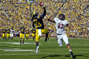 Photo -   Michigan wide receiver Jerald Robinson (83) attempts to catch a pass in the end zone while under pressure from defensive back Darren Thellen (27) in the first quarter of an NCAA college football game, Saturday, Sept. 15, 2012, in Ann Arbor, Mich. The pass was incomplete. (AP Photo/Tony Ding)