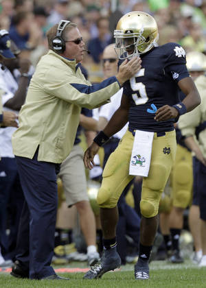 Photo -   Notre Dame coach Brian Kelly, left, gives a play to quarterback Everett Golson during the first half of an NCAA college football game against Purdue in South Bend, Ind., Saturday, Sept. 8, 2012. (AP Photo/Michael Conroy)