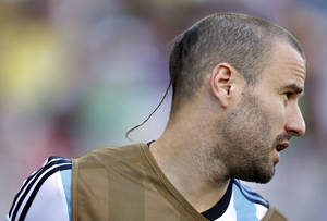 Photo - FILE - In this July 1, 2014, file photo, Argentina's Rodrigo Palacio warms-up on the touchline during the World Cup round of 16 soccer match between Argentina and Switzerland at the Itaquerao Stadium in Sao Paulo, Brazil.  Palacio with his shaved head except for a rat's tail at the back, arguably has the most jaw-dropping haircut at the World Cup. (AP Photo/Frank Augstein, File)