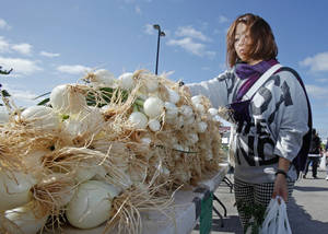 Photo - Yui Takazawa, of Oklahoma City, looks at an offering of onions at last year's Norman Farm Market.