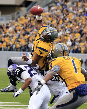 photo -   West Virginia quarterback Geno Smith (12) is tackled at the goal line by TCU&#039;s Kevin White (25) and Joel Hasley (36) during the first half of their NCAA college football game in Morgantown, W.Va., on Saturday, Nov. 3, 2012. (AP Photo/Christopher Jackson)  
