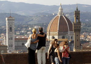 Photo - In this photo taken on July 8, 2013 a couple looks at the Florence Santa Maria del Fiore Basilica, with Giotto's bell tower, left, Brunelleschi's dome, from Forte Belvedere, Italy. Kim Kardashian and Kanye West will get married at Florence's imposing 16th century Belvedere Fort on May 24, a spokeswoman at the Florence mayor's office said Friday, May 16, 2014. The couple rented the fort, located next to Florence's famed Boboli Gardens, for 300,000 euros ($410,000). Di Lupo said a Protestant minister will preside, spokeswoman Elisa Di Lupo said. The 36-year-old rapper proposed to the reality star on her 33rd birthday in October 2013 renting out San Francisco's AT&T Park for the occasion. There has been no explicit confirmation from either Kardashian or West. In an email Thursday to The Associated Press, Kardashian's representative Ina Treciokas said she wasn't able to comment on reports about the nuptials. (AP Photo/Francesco Bellini)