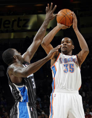 Photo - Oklahoma City's Kevin Durant (35) takes a shot over Brandon Bass (30) of Orlando during the NBA basketball game between the Orlando Magic and Oklahoma City Thunder in Oklahoma City, Thursday, January 13, 2011. Photo by Nate Billings, The Oklahoman
