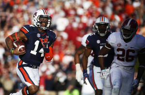Photo - Auburn quarterback Nick Marshall (14) scores a touchdown as Alabama defensive back Landon Collins (26) chases him during the first half of an NCAA college football game Saturday, Nov. 30, 2013, outside of Jordan-Hare Stadium in Auburn, Ala. (AP Photo/Opelika-Auburn News, Albert Cesare)