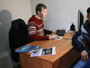 Photo - FILE - In this Jan. 30, 2013 file photo, Semyon Simonov helps a migrant worker at his office in Sochi, where he provides free legal aid to workers building Olympic venues. A lawyer for Simonov and Moscow-based prisoner rights activist Nikolai Levshits said Friday, Jan. 31, 2014, that the two men have filed a lawsuit against the Sochi Olympics organizers after they were barred from attending the games. Simonov has documented widespread abuse of migrant workers at Olympic construction sites. (AP Photo/Igor Yakunin, File)