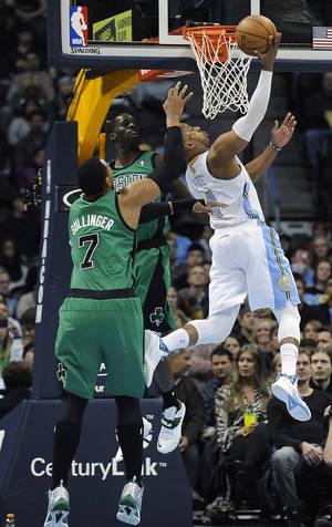 Photo - Denver Nuggets guard Randy Foye, right, scores over Boston Celtics  forward Jared Sullinger, left, and Brandon Bass, center, in the first half of an NBA basketball game on Tuesday, Jan. 7, 2014, in Denver.  (AP Photo/Chris Schneider)