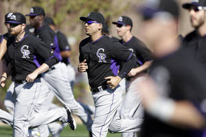 Photo - Colorado Rockies left fielder Carlos Gonzalez, center, jogs with teammates during a spring training baseball practice Wednesday, Feb. 26, 2014, in Scottsdale, Ariz. (AP Photo/ Gregory Bull)