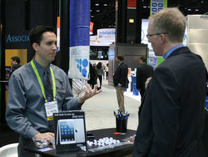 Photo - Steven Martinez, who works at the Oklahoma Center for the Advancement of Science and Technology, greets visitors Wednesday at the OKBio booth. <strong>unknown - JIM STAFFORD</strong>