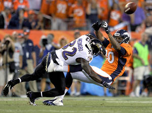 Photo - FILE - In this Sept. 5, 2013 file photo, Baltimore Ravens strong safety James Ihedigbo (32) breaks up a pass intended for Denver Broncos tight end Julius Thomas (80) during the first half of an NFL football game, in Denver. A person familiar with negotiations says the Detroit Lions and Ihedigbo have agreed to a two-year contract. The person spoke Tuesday, March 25, 2014, to The Associated Press on condition of anonymity because the deal had not been announced. Ihedigbo made 99 tackles and had three interceptions for the Baltimore Ravens last year.(AP Photo/Jack Dempsey)