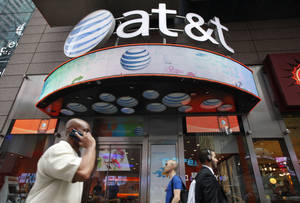 Photo - FILE - In this July 11, 2013 photo, a man uses a cell phone as he walks past an AT&T store in New York. AT&T reports quarterly earnings on Tuesday, Jan. 28, 2014. (AP Photo/Mark Lennihan, File)