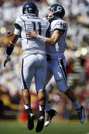 Photo -   Connecticut quarterback Scott McCummings, left, celebrates with Chandler Whitmer after McCummings scored a touchdown in the first half of an NCAA college football game against Maryland in College Park, Md., Saturday, Sept. 15, 2012. Connecticut won 24-21. (AP Photo/Patrick Semansky)