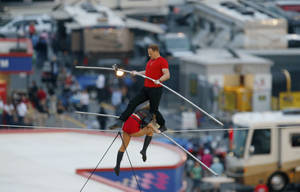 Photo - Nik Wallenda steps over his sister Lijana Wallenda as they perform on a tightrope before the NASCAR Sprint Cup Series auto race at Charlotte Motor Speedway in Concord, N.C., Saturday, Oct. 12, 2013. (AP Photo/Chris Keane)