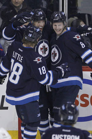 Photo - Winnipeg Jets' Bryan Little (18), Blake Wheeler (26) and Jacob Trouba (8) celebrate Wheeler's goal against the Minnesota Wild during first-period NHL hockey game action in Winnipeg, Manitoba, Friday, Dec. 27, 2013. (AP Photo/The Canadian Press, John Woods)