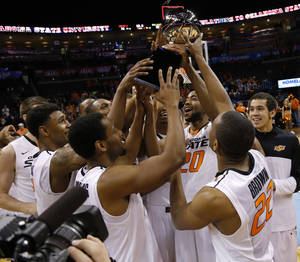 Photo - The Oklahoma State Basketball team celebrates with the trophy after winning the All-College Classic basketball game between Oklahoma State University and Louisiana Tech at Chesapeake Energy Arena in Oklahoma City, Okla., Saturday, Dec. 14, 2013. Photo by Bryan Terry, The Oklahoman