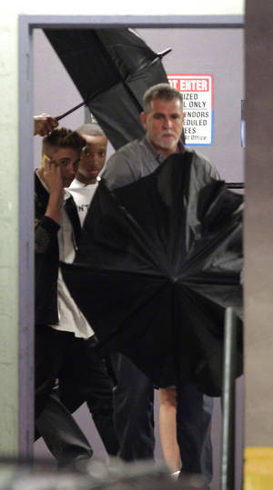 Photo - Justin Bieber, left, leaves his lawyers office in Miami, Thursday, March 6, 2014, after testifying in a civil deposition regarding an alleged assault on a photographer last year. (AP Photo/Luis M. Alvarez)
