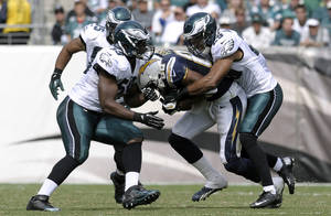 Photo - San Diego Chargers' Malcom Floyd, center, tackled by Philadelphia Eagles' DeMeco Ryans, left, and Nate Allen during the second half of an NFL football game on Sunday, Sept. 15, 2013, in Philadelphia. (AP Photo/Michael Perez)