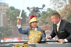 "Photo - ESPN ""College GameDay"" analyst Lee Corso, left, suffers a cut lip after an impromptu sword fight with analyst Kirk Herbstreit, right, during the show last Saturday at USC. Corso was correct in picking USC to upset Stanford. ESPN Photo <strong>Scott Clarke - Scott Clarke</strong>"